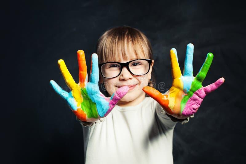 Dzieciak cieszy się jego obraz Śliczna dziecko dziewczyna z kolorowymi rękami na sali lekcyjnej blackboard tle Sztuki i kreatywni obraz stock