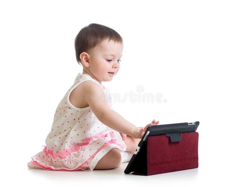 Dzieciak dziewczyna bawić się z cyfrową pastylką fotografia royalty free