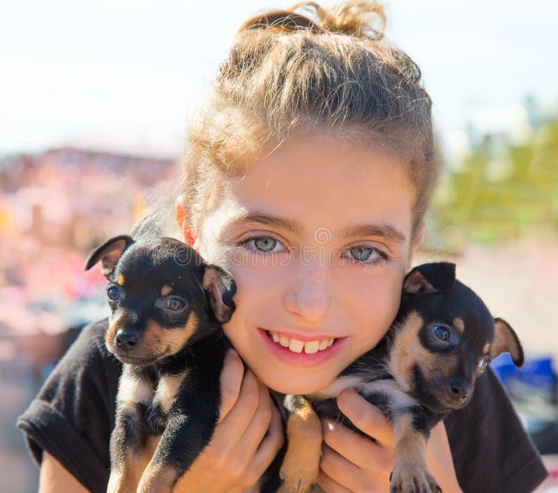 Dzieciak dziewczyna bawić się z szczeniaków psów ono uśmiecha się zdjęcie royalty free