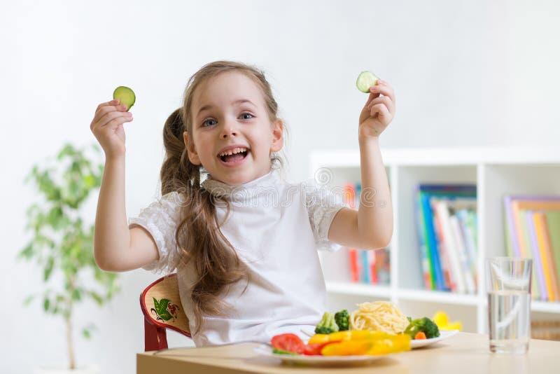 Dzieciak dziewczyna je zdrowego jedzenie w dziecinu lub w domu obrazy royalty free