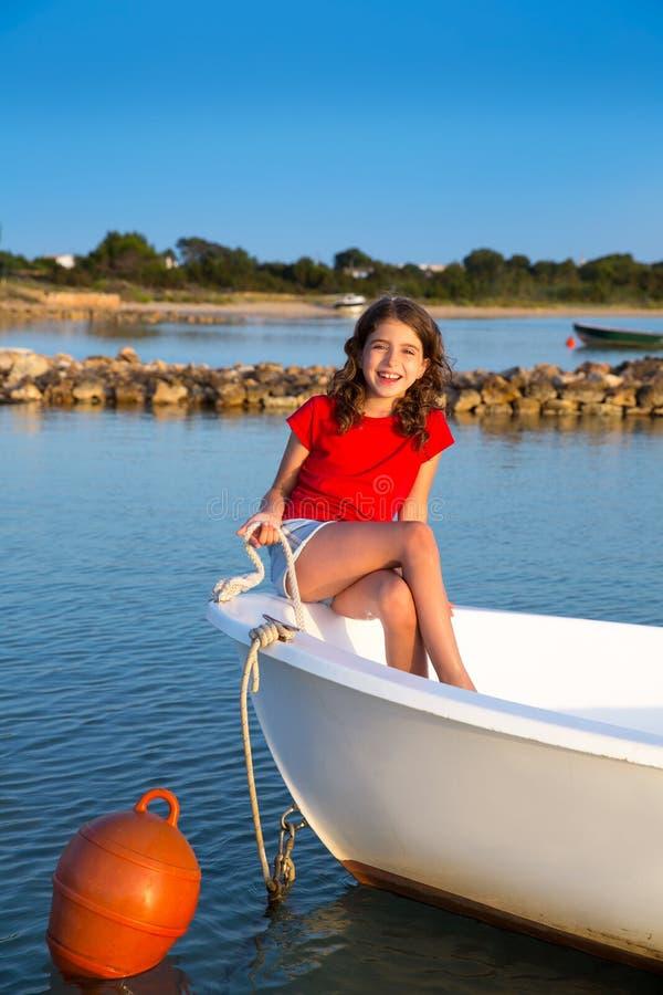 Dzieciak dziewczyna udaje być żeglarzem w łódkowatym łęku przy Formentera fotografia stock
