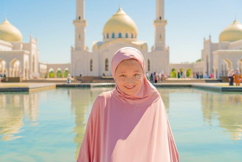 Dzieciak dziewczyna w różowym hijab siedzi obok białego meczetu i ono uśmiecha się Na ulicie zdjęcie royalty free