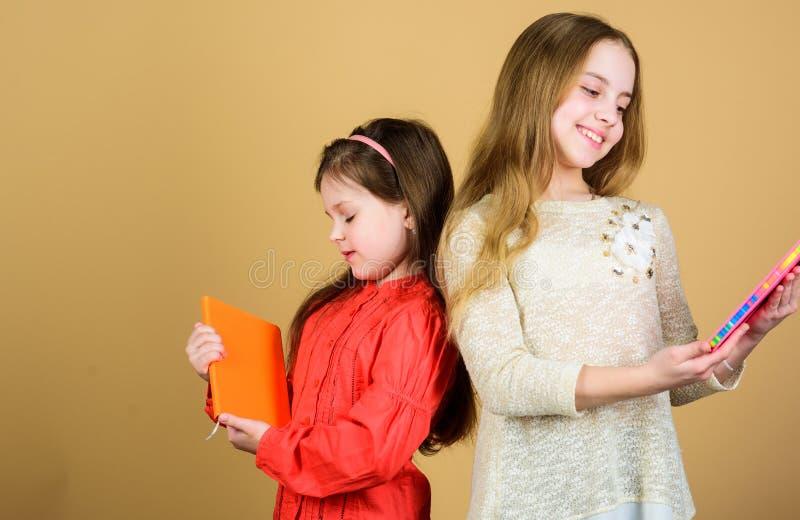 Dzieciak dziewczyny z ksi??kami lub notepads Edukacja i dzieciak literatura Ulubiona bajka Siostra wyboru ksi??ki czyta? obraz royalty free