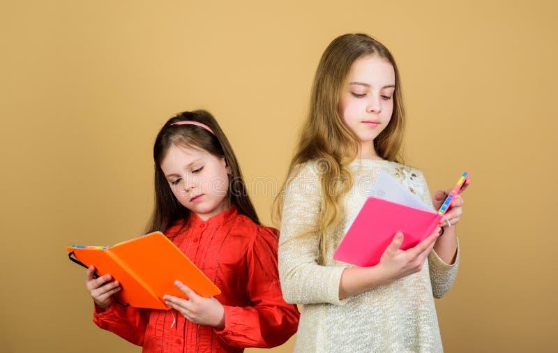 Dzieciak dziewczyny z ksi??kami lub notepads Edukacja i dzieciak literatura Ulubiona bajka Siostra wyboru książki czytać obrazy royalty free