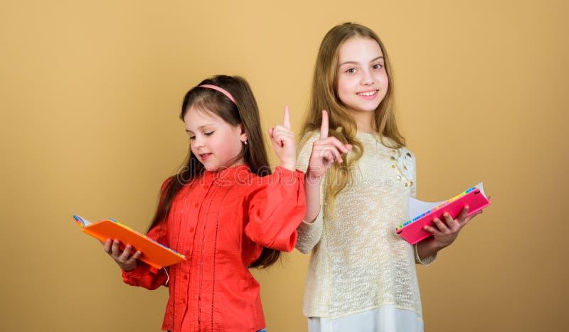 Dzieciak dziewczyny z ksi??kami lub notepads Edukacja i dzieciak literatura Ulubiona bajka tylna szko?y Siostra wyboru książki zdjęcia royalty free