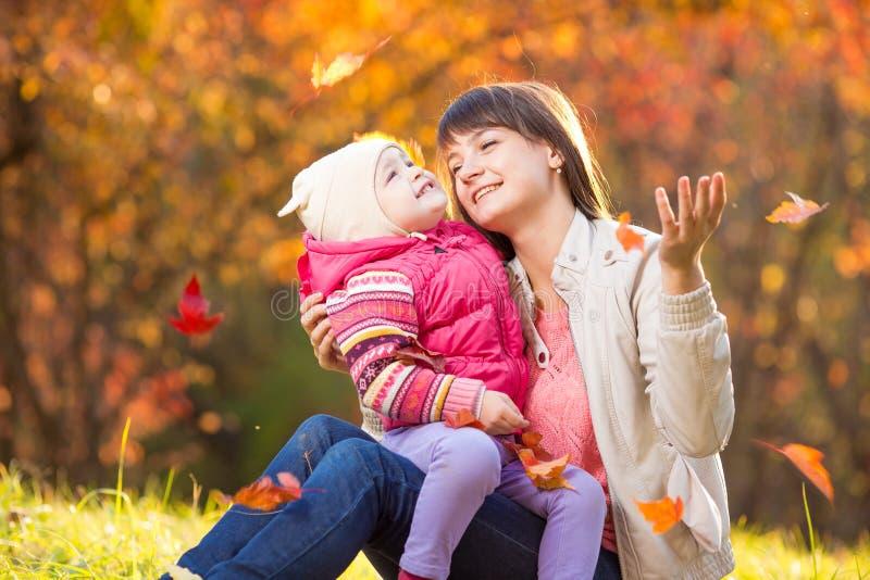 Dzieciak i piękny matki bawić się plenerowi w jesień parku obraz stock