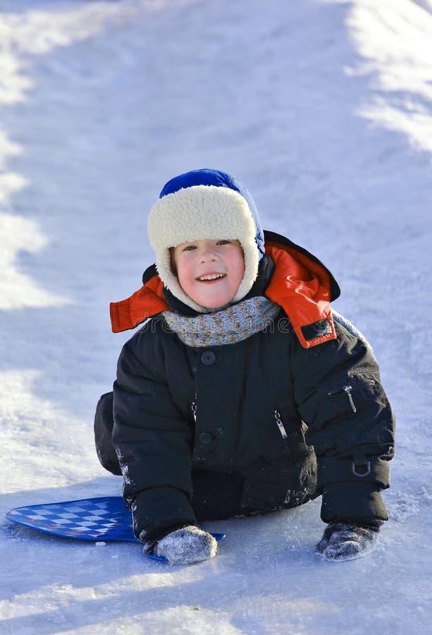 Dzieciak jedzie zamarzniętego wzgórze zdjęcie royalty free
