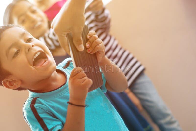 Dzieciak krzyczy podczas gdy mateczny próbować brać oddalonego telefon komórkowego z dzieciakami śmia się od za w domu zdjęcia stock