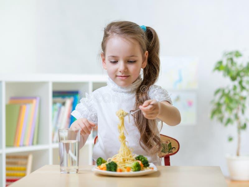 Dzieciak mała dziewczynka je jarskiego jedzenie lub dziecina w domu zdjęcie royalty free