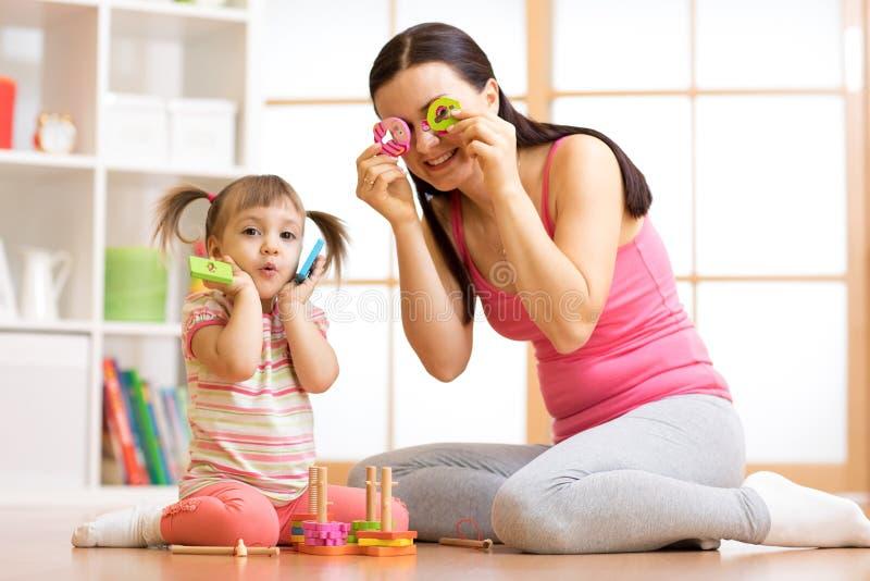 Dzieciak matka i dziewczyna zabawę z łamigłówek zabawkami Młodej kobiety i dziecka berbecia obsiadanie na podłoga i bawić się edu obrazy stock