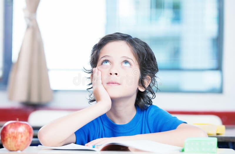 Dzieciak myśleć patrzeć oddolny przy szkolnym biurkiem zdjęcia royalty free