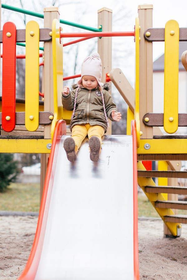 Dzieciak na boisku w jesień parku Dziecko na obruszeniu i hu?tawce na pogodnym spadku dniu Preschool lub dziecina jard Plenerowa  zdjęcia royalty free