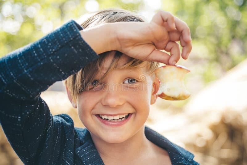 Dzieciak na jesień wakacje w gospodarstwie rolnym Uśmiechnięta chłopiec trzyma gryźć jabłka z jeden ręką Walkoweru lato - cześć j obrazy royalty free