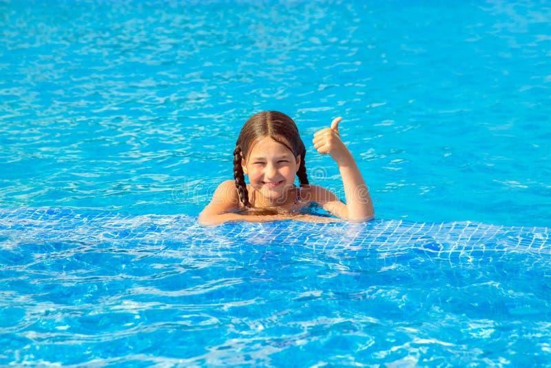 Dzieciak pływa w basenie i pokazuje kciuk w górę symbolu zdjęcie stock