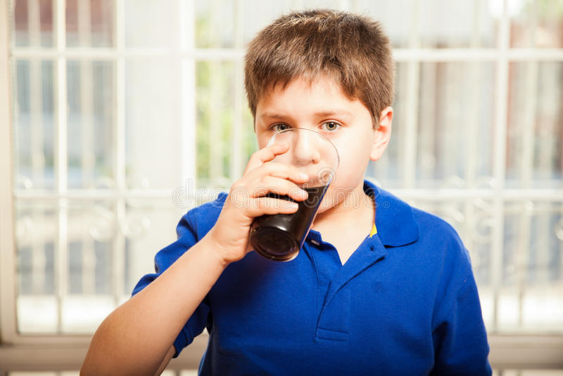 Dzieciak pije sodę od szkła zdjęcie royalty free