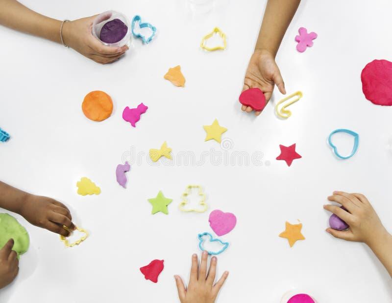 Dzieciak ręki z kolorowymi glinami na bielu stole obraz stock