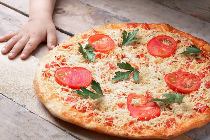 Dzieciak ręki z Margarita pizzą z pomidorem i dwa czerwieni chili na popielatym stole, odgórnym widoku i miejscu dla teksta, zdjęcie stock