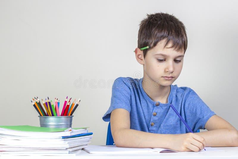 Dzieciak robi pracie domowej przy sto?em Skupiająca się chłopiec z ołówkiem za jego ucho pisze z ołówkiem obraz stock