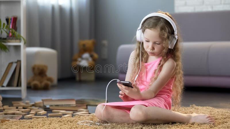 Dzieciak s?ucha muzyka na smartphone w he?mofonach, uzale?niaj?cym si? technologia zdjęcie stock