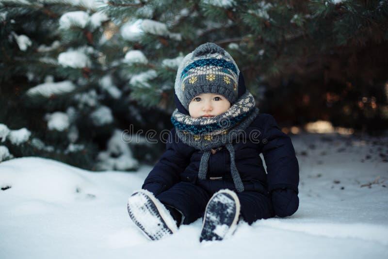 Dzieciak siedzi w śniegu w błękitnych kombinezonach zdjęcia royalty free