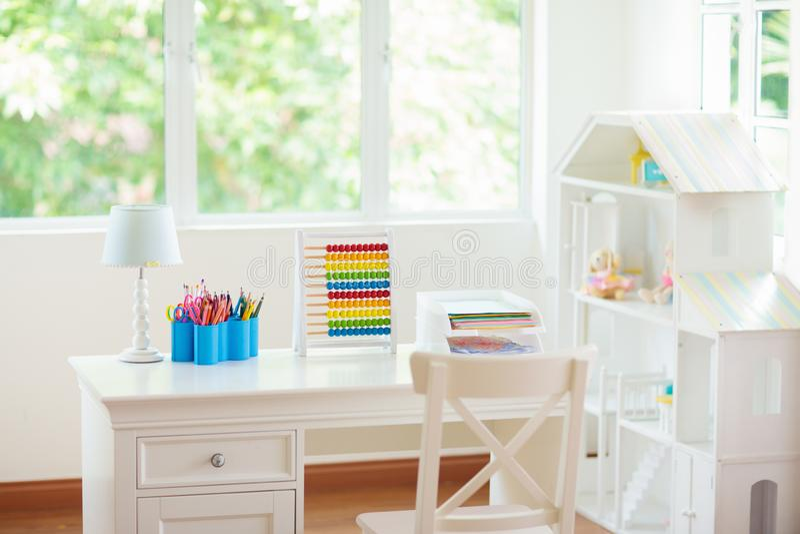 Dzieciak sypialnia z drewnianym biurka i lali domem obrazy stock