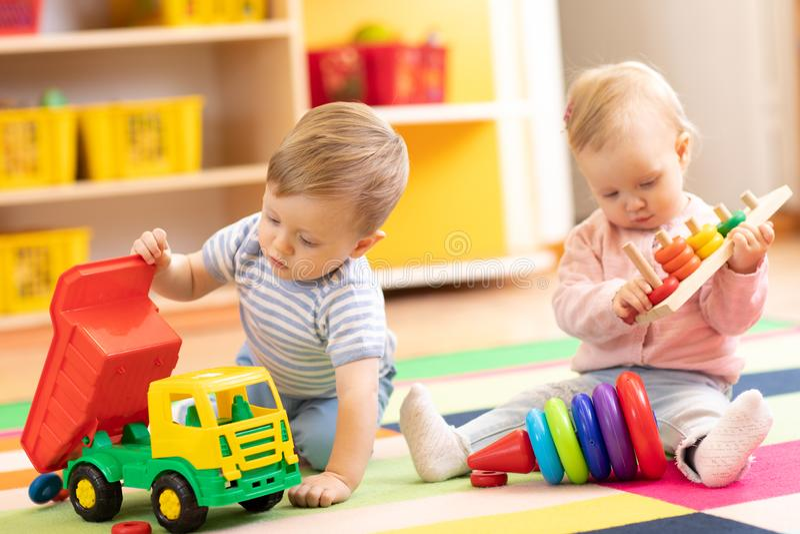 Dzieciak sztuka z edukacyjnymi zabawkami Dzieci siedzą na dywaniku w sztuka pokoju lub dziecinu w domu Berbeć chłopiec z zabawką fotografia stock