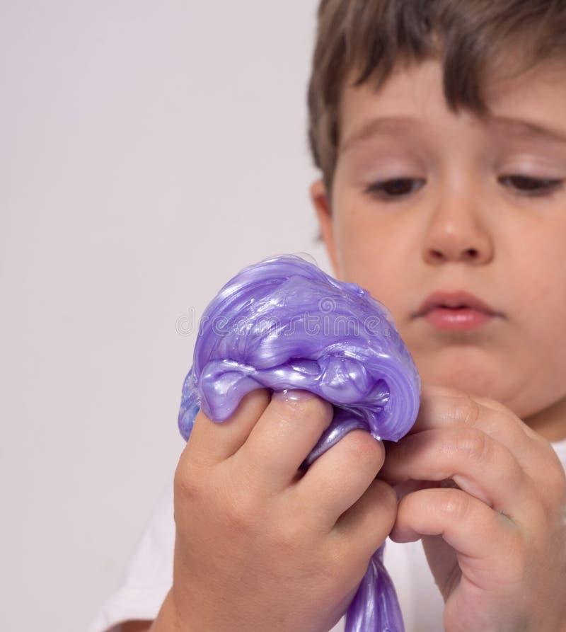 Dzieciak sztuka z szlamowym Chłopiec rozciągliwości handgum lub zabawka szlamowi obrazy royalty free