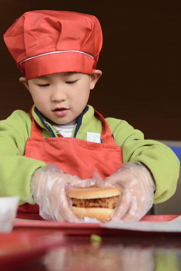 Dzieciak uczy się robić hamburgerowi zdjęcia stock