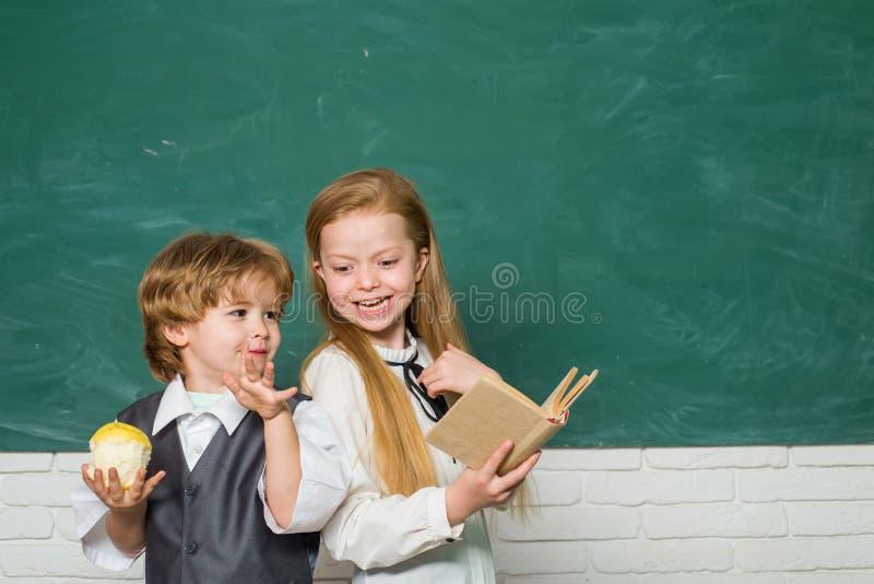Dzieciak uczy si? w klasie na tle blackboard Szko?a dzieciaki Śliczna mała preschool dzieciak chłopiec z małe dziecko dziewczyną obrazy royalty free