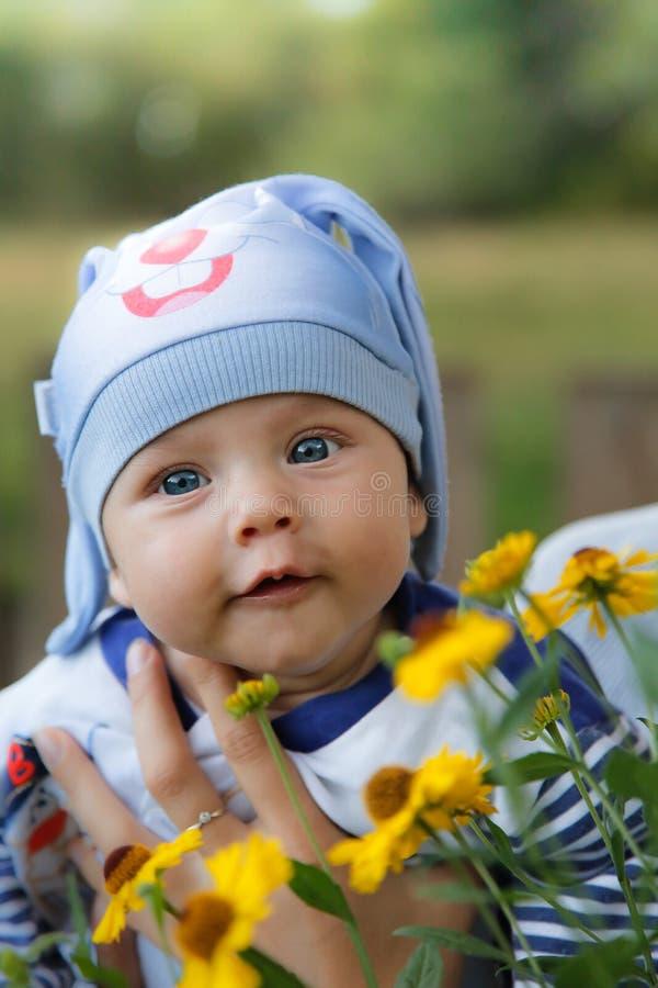 Dzieciak w błękitnym królika kostiumu w wiosce wśród kwiatów, obraz royalty free