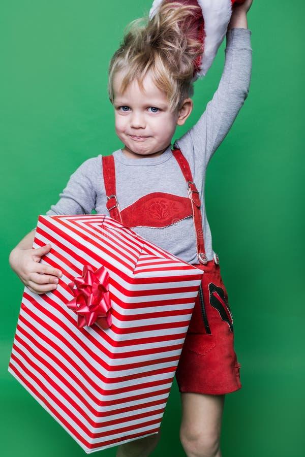 Dzieciak w czerwonym kostiumu karłowatego mienia prezenta i rzutu Święty Mikołaj Bożenarodzeniowa nakrętka niegrzeczne dziecko obrazy royalty free