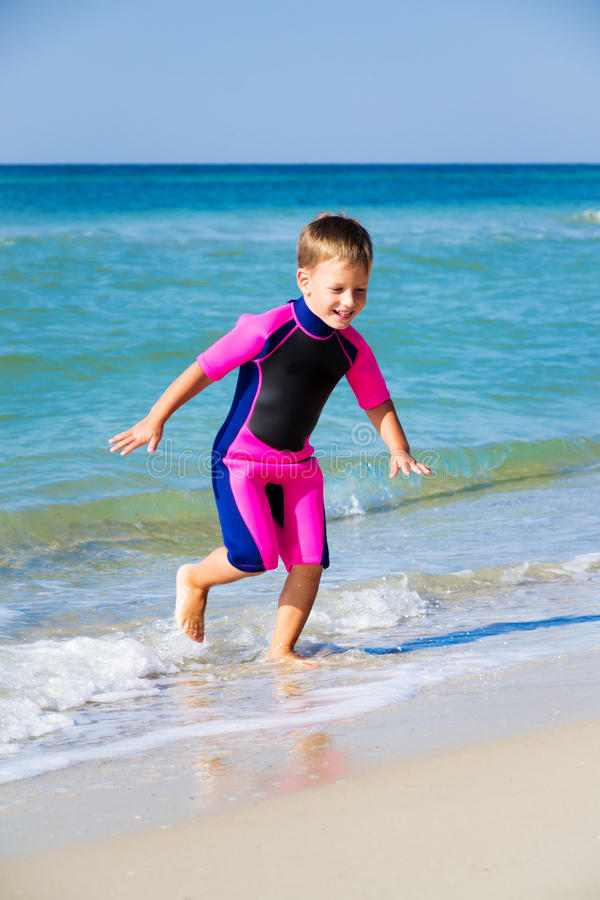 Dzieciak w jego nurkowym kostiumu opuszcza wodę przy plażą zdjęcia stock