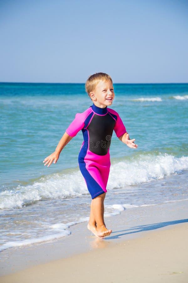 Dzieciak w jego nurkowym kostiumu opuszcza wodę przy plażą obrazy royalty free