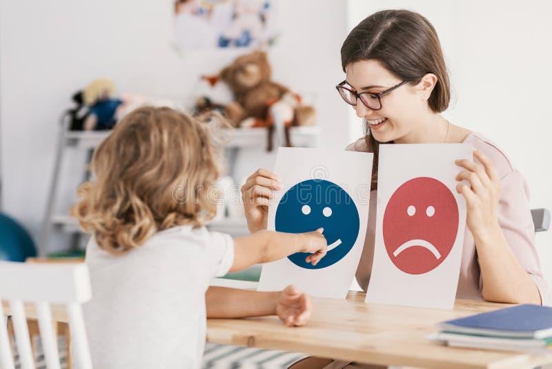 Dzieciak wskazuje przy grafiką z smiley twarzą podczas psychicznego obraz royalty free