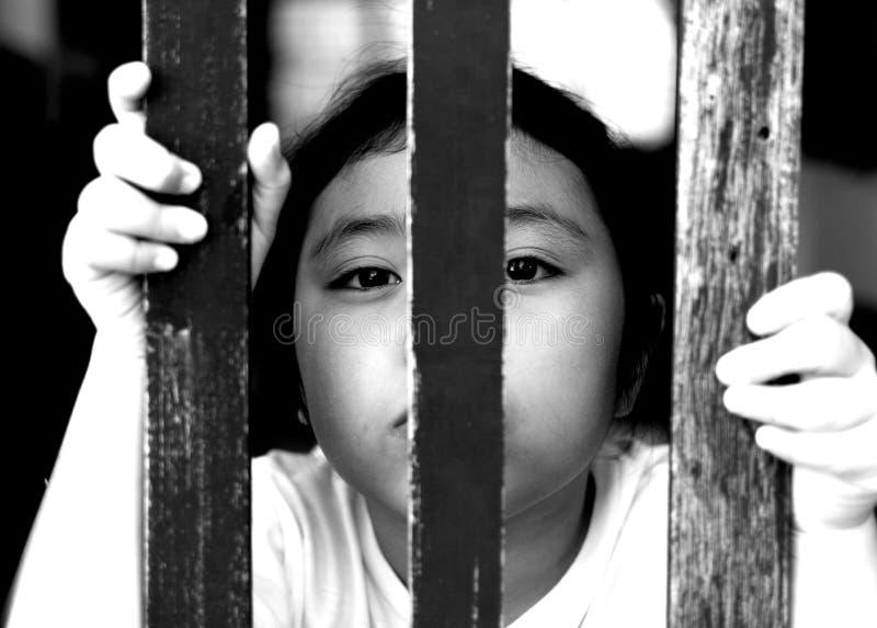 Dzieciak z drewna ogrodzeniem, czuje żadny wolność, czarny i biały fotografia obrazy stock
