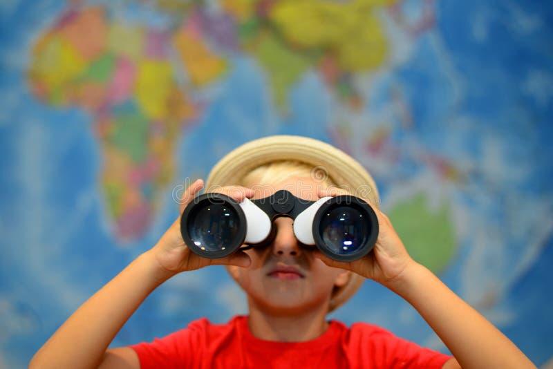 Dzieciak z lornetkami jest przyglądający wokoło Przygody i podróży pojęcie kreatywne tło Chłopiec bawić się w kapitanie zdjęcia royalty free