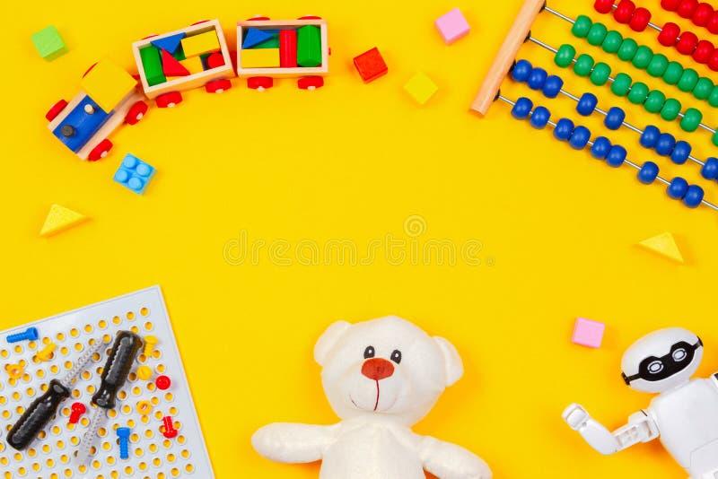Dzieciak zabawek tło Miś, drewniany pociąg, robot, kolorowi bloki, zabawkarski narzędzie zestaw, abakus na żółtym tle fotografia stock