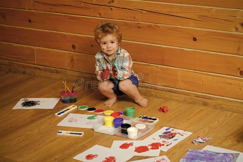 Dzieciaka bawić się i uczenie Chłopiec malarza obraz na drewnianej podłoga zdjęcia stock