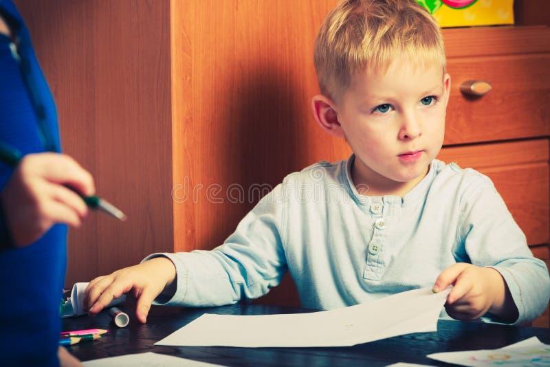 Dzieciaka bawić się, rysuje obrazki na papierze obraz stock