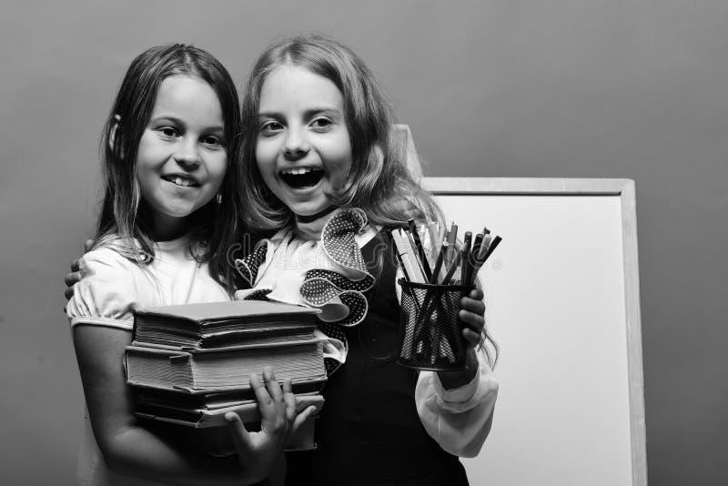 Dzieciaka chwyta książki i kolorowe szkolne dostawy Dziewczyny z szczęśliwymi ono uśmiecha się twarzami i materiały obrazy royalty free