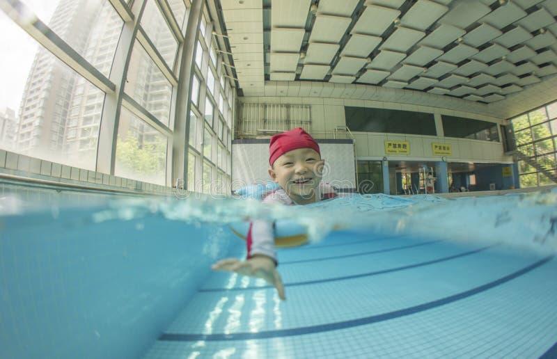 Dzieciaka dopłynięcie w basenie z uśmiechem fotografia royalty free
