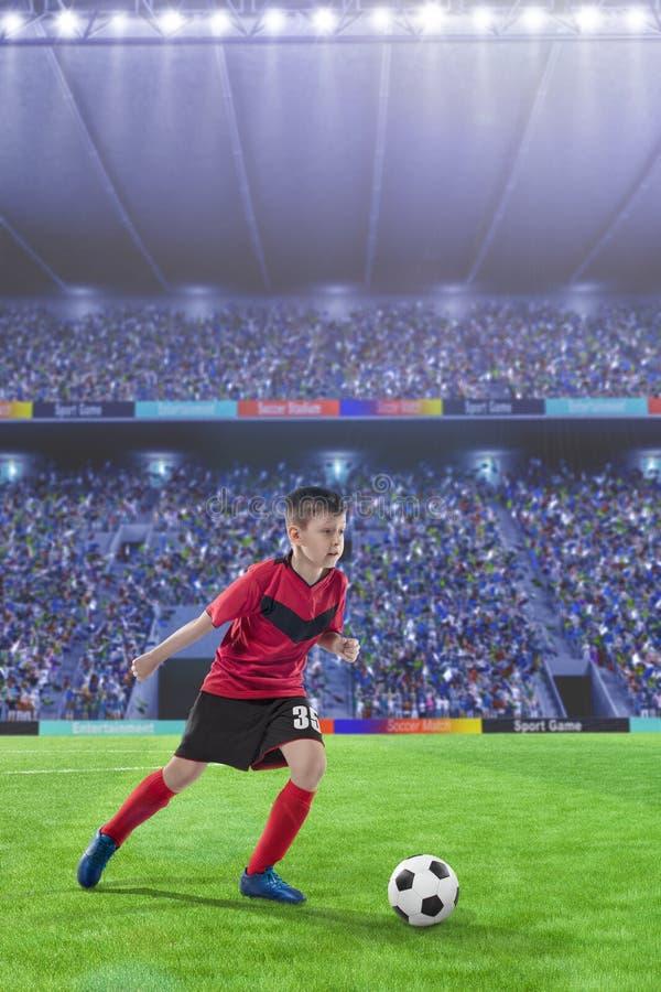 Dzieciaka gracz futbolu drybluje na boisko do piłki nożnej zdjęcia stock