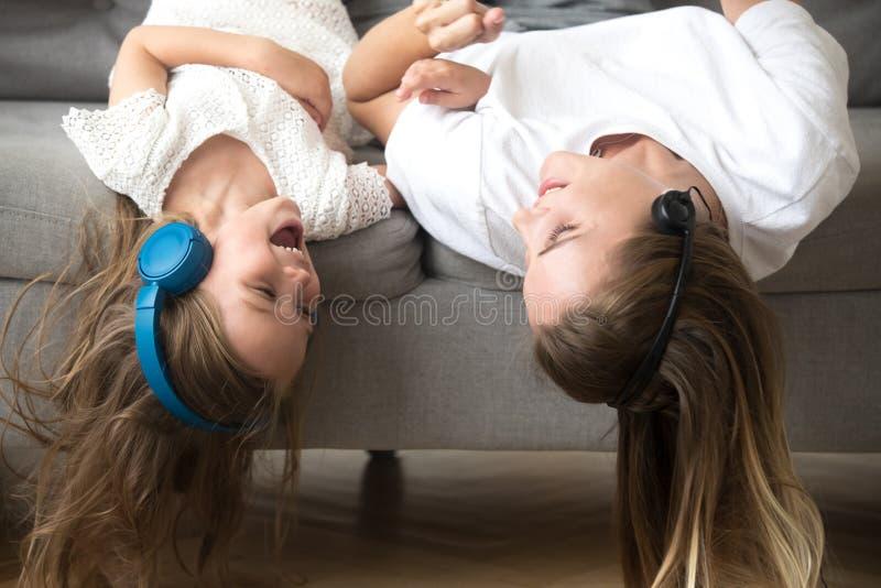 Dzieciaka i matki kłamać do góry nogami w hełmofonach cieszy się muzykę obrazy stock