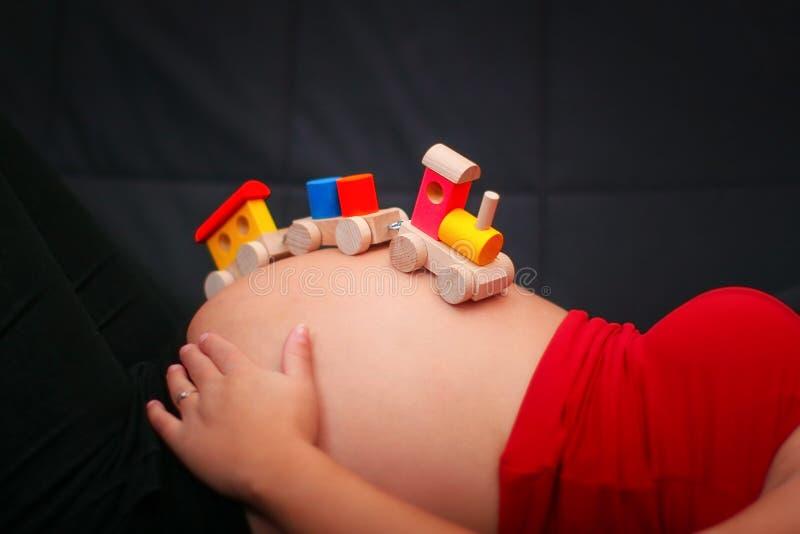 Dzieciaka pociągu drewniana zabawka na ciężarnym brzuchu Dziecka oczekiwanie conc zdjęcie stock