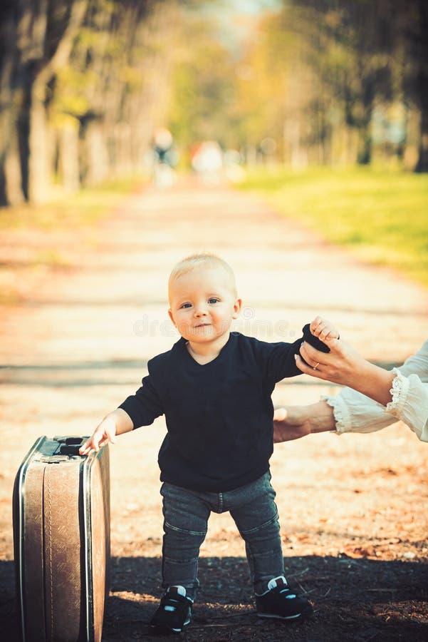 Dzieciaka podróżnik z bagażem plenerowym Mała chłopiec niesie retro walizkę na naturalnym krajobrazie Dziecko podróż dla wakacje  fotografia royalty free