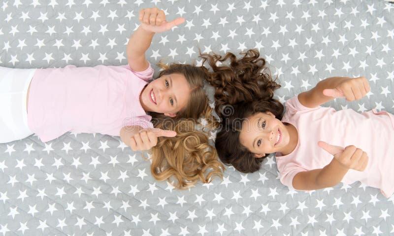 Dzieciaka przedstawienia aprobat gest Dziewczyn dzieci na łóżkowym odgórnym widoku Piżamy przyjęcia pojęcie chciał po prostu zaba obraz royalty free