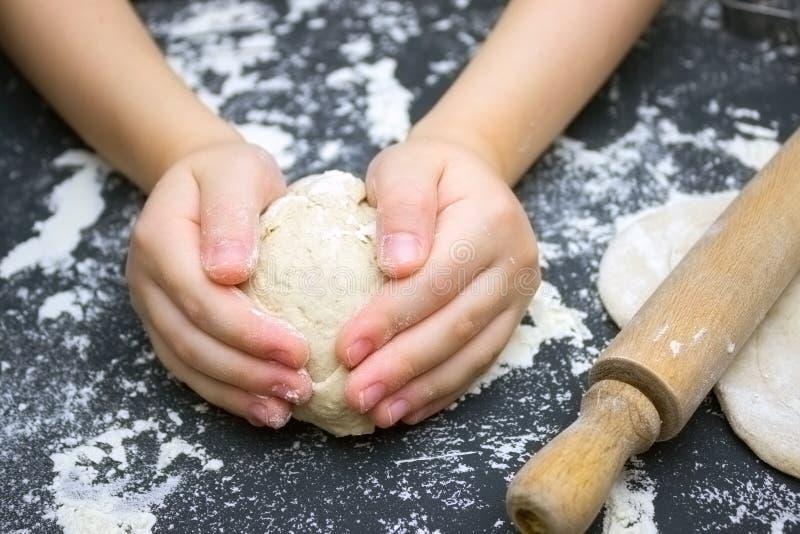 Dzieciaka ` s ręki, niektóre mąka, pszeniczny ciasto i toczna szpilka na czarnym stole, Dzieci wręczają robić żyta ciastu dla pop obrazy stock