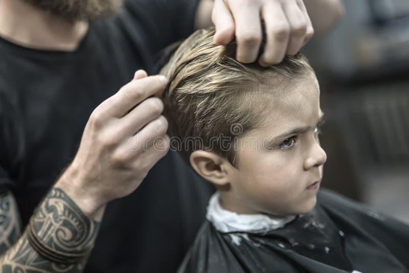 Dzieciaka ` s włosiany tytułowanie w zakładzie fryzjerskim obrazy stock