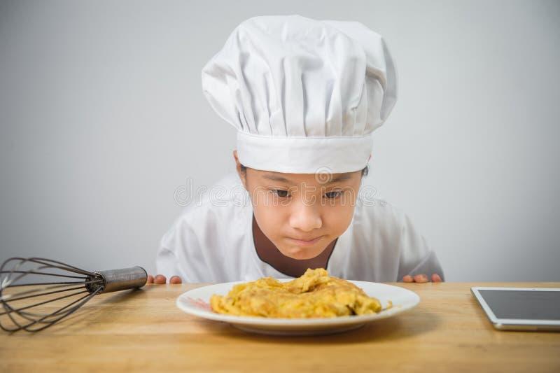 Dzieciaka szef kuchni jest przyglądający omlet w naczyniu obrazy stock