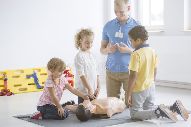 Dzieciaki ćwiczy pierwsza pomoc kroki obraz royalty free